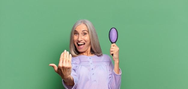 Mulher bonita de cabelos grisalhos acordando e de pijama