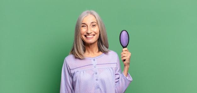 Mulher bonita de cabelos grisalhos acordando e vestindo pijama