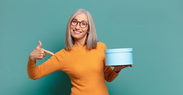 Mulher bonita de cabelos grisalhos com caixa de presente