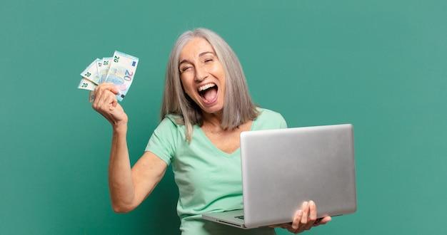 Mulher bonita de cabelos grisalhos com dinheiro e um laptop