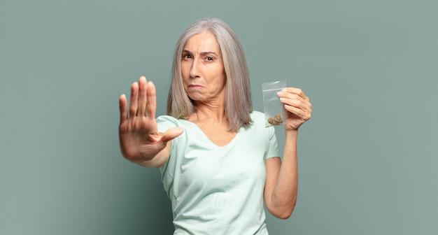 Mulher bonita de cabelos grisalhos com maconha