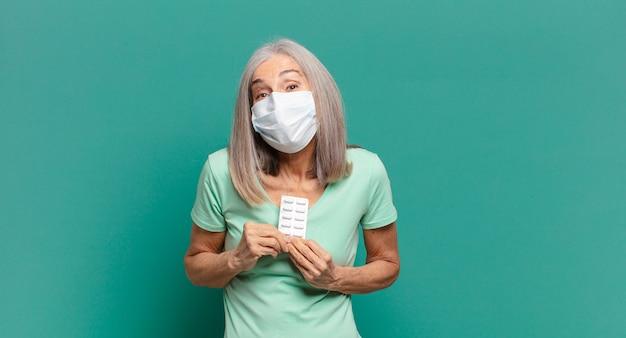 Mulher bonita de cabelos grisalhos com máscara protetora e comprimidos