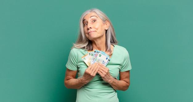 Mulher bonita de cabelos grisalhos com notas