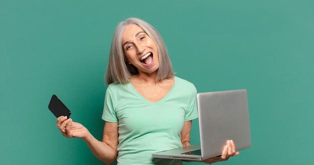Mulher bonita de cabelos grisalhos com um celular e um laptop