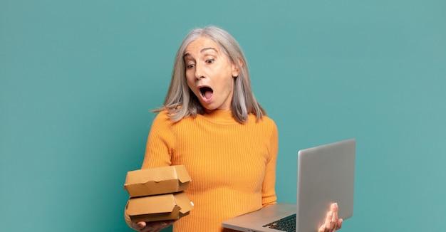 Mulher bonita de cabelos grisalhos com um laptop. conceito de comida rápida para viagem