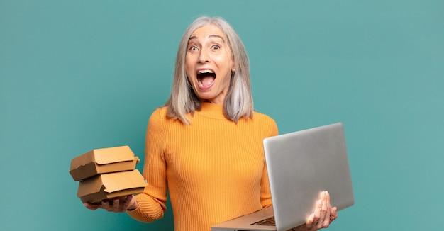 Mulher bonita de cabelos grisalhos com um laptop e comida para levar