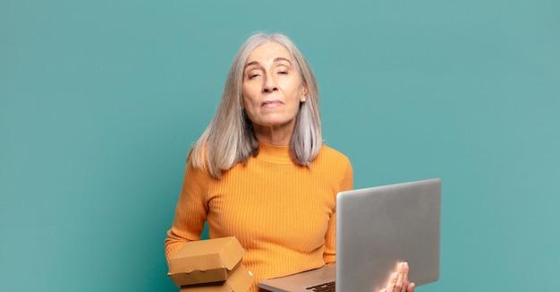 Mulher bonita de cabelos grisalhos com um laptop