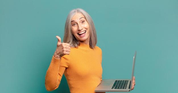 Mulher bonita de cabelos grisalhos com um laptop.