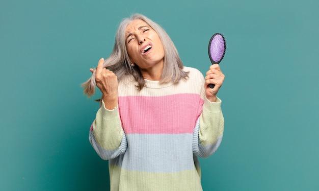 Mulher bonita de cabelos grisalhos com uma escova de cabelo