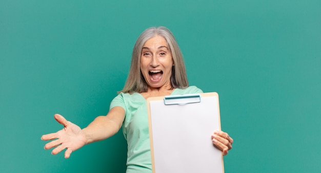 Mulher bonita de cabelos grisalhos mostrando um pedaço de papel vazio