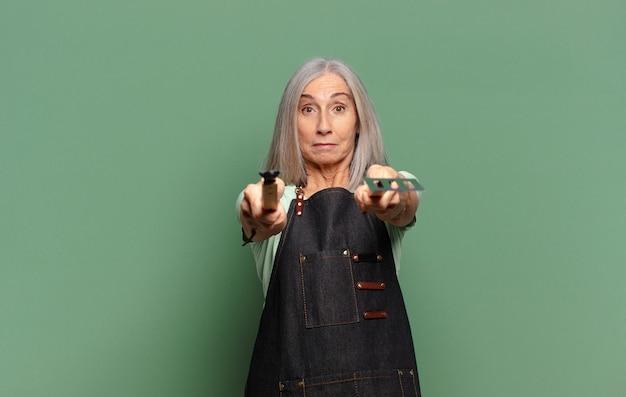 Mulher bonita de cabelos grisalhos pronta para preparar o churrasco