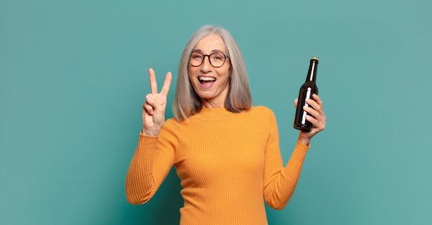 Mulher bonita de cabelos grisalhos tomando uma cerveja