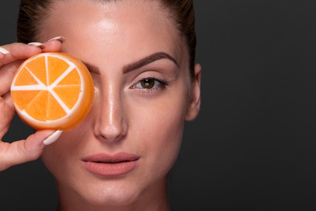 Mulher bonita de close-up com produto de cuidados com a pele