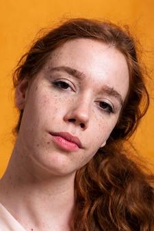 Mulher bonita de close-up com sardas e olhos castanhos