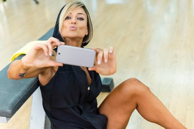 Mulher bonita de esportes fazendo selfie em smartphone no ginásio.