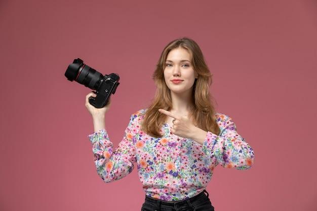 Mulher bonita de frente mostra sua fotocâmera com o dedo indicador
