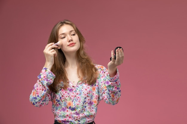 Mulher bonita de frente usando um pincel de pó cosmético para a maquiagem