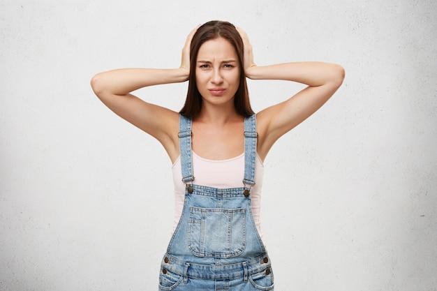 Mulher bonita de macacão jeans, sofrendo de barulho alto e dor de cabeça, cobrindo a cabeça e os ouvidos com as mãos, parecendo chateado isolado. emoções, sentimentos e reações humanas