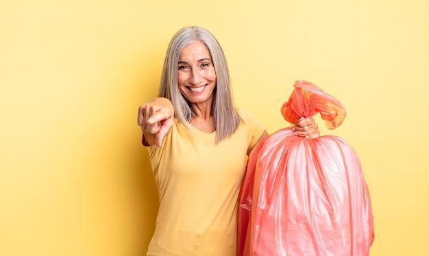 Mulher bonita de meia-idade apontando para a câmera escolhendo você. saco plástico garbaje