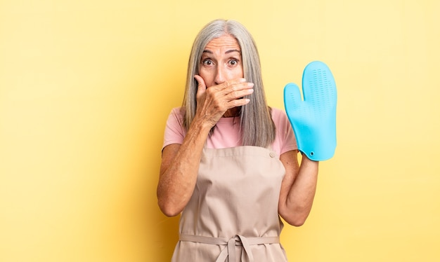 Mulher bonita de meia-idade cobrindo a boca com as mãos com um choque. conceito de luva de forno