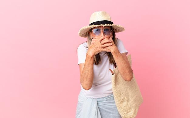 Mulher bonita de meia-idade cobrindo a boca com as mãos com um choque. conceito de verão
