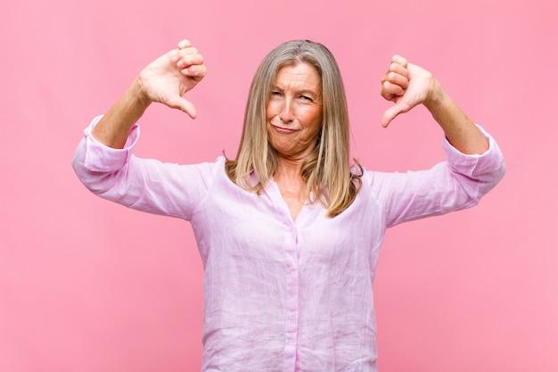 Mulher bonita de meia-idade com aparência triste, decepcionada ou zangada, mostrando o polegar para baixo em desacordo e sentindo-se frustrada