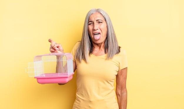 Mulher bonita de meia-idade com atitude alegre e rebelde, brincando e mostrando a língua. conceito de gaiola ou prisão para animais de estimação