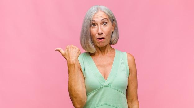 Mulher bonita de meia-idade com boca aberta, parecendo horrorizada e chocada por causa de um erro terrível, levando as mãos à cabeça