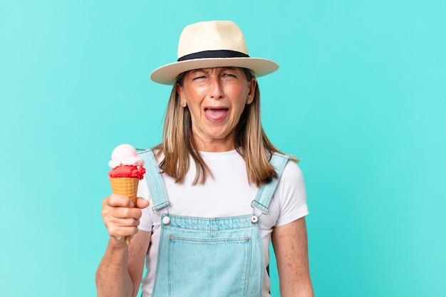 Mulher bonita de meia-idade com chapéu e segurando um sorvete. conceito de verão