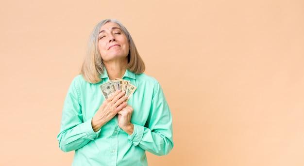 Mulher bonita de meia idade com notas de dólar contra a parede do espaço de cópia