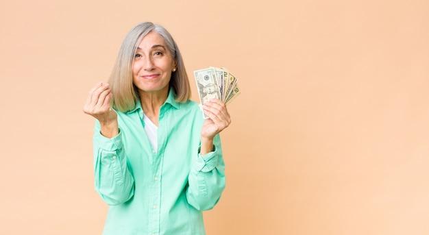 Mulher bonita de meia idade com notas de dólar contra a parede