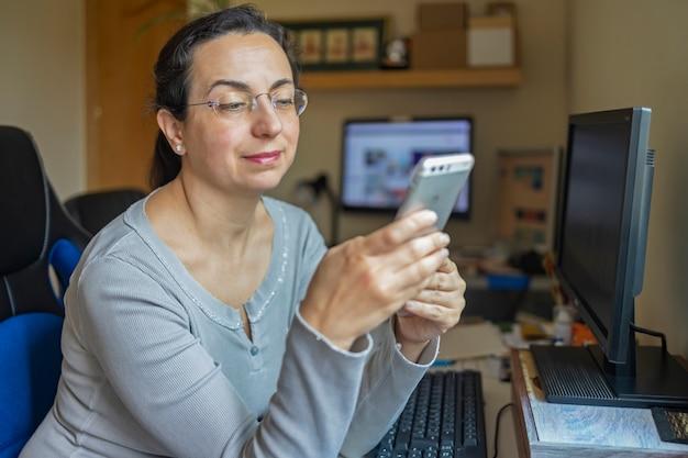 Mulher bonita de meia idade com óculos, trabalhando em casa, escritório com computador