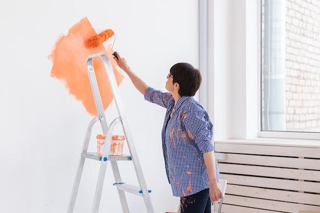 Mulher bonita de meia-idade com rolo de pintura dentro de casa. redecoração, reforma, conserto de apartamentos
