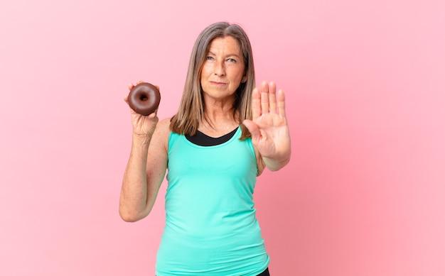 Mulher bonita de meia idade com um donut
