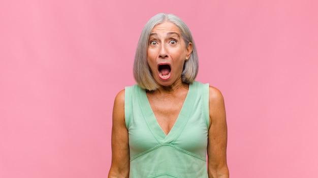 Mulher bonita de meia-idade com uma expressão boba, louca e surpresa, bochechas bufantes, sentindo-se recheada, gorda e cheia de comida