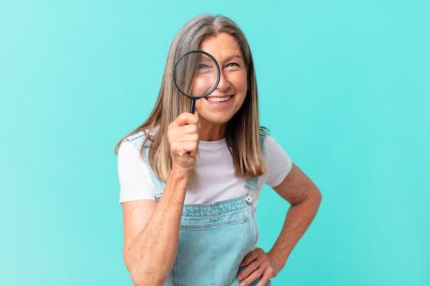 Mulher bonita de meia-idade com uma lupa. conceito de busca