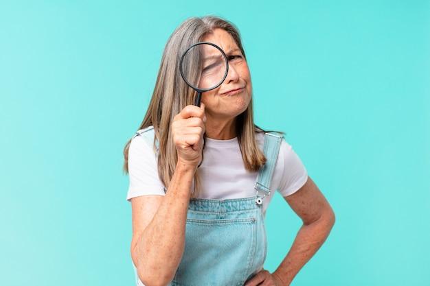 Mulher bonita de meia-idade com uma lupa. conceito de pesquisa