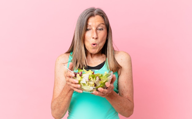 Mulher bonita de meia-idade com uma salada. conceito de dieta