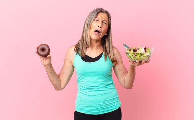 Mulher bonita de meia-idade comendo uma salada e donut
