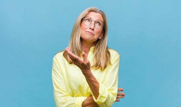 Mulher bonita de meia-idade cruzando os dedos ansiosamente e esperando por boa sorte com um olhar preocupado