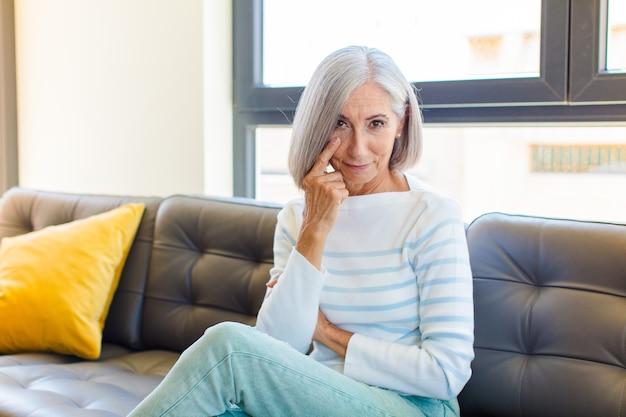 Mulher bonita de meia-idade de olho em você, sem confiar, observando e ficando alerta e vigilante