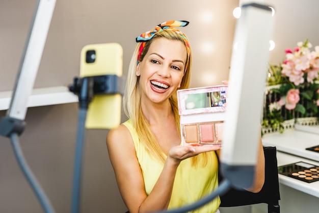 Mulher bonita de meia-idade e beleza profissional compõem um tutorial de maquiagem de gravação de vlogger ou blogger para compartilhar no site ou nas redes sociais.