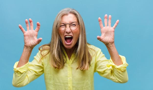 Mulher bonita de meia-idade encolhendo os ombros com uma expressão estúpida, maluca, confusa e perplexa, sentindo-se irritada e sem noção