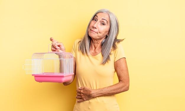 Mulher bonita de meia-idade encolhendo os ombros, sentindo-se confusa e incerta. conceito de gaiola ou prisão para animais de estimação