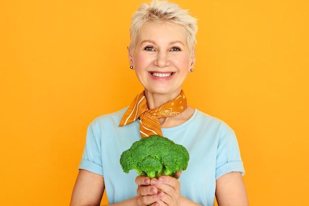 Mulher bonita de meia idade enérgica com cabelo curto grisalho posando isolado com brócolis verde nas mãos, vai fazer salada orgânica saudável.