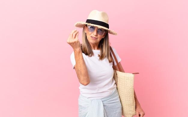 Mulher bonita de meia-idade fazendo capice ou gesto de dinheiro, dizendo para você pagar. conceito de verão
