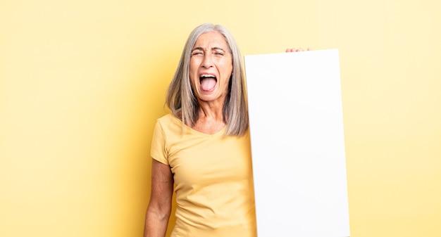 Mulher bonita de meia-idade gritando agressivamente, parecendo muito zangada. conceito de tela vazia