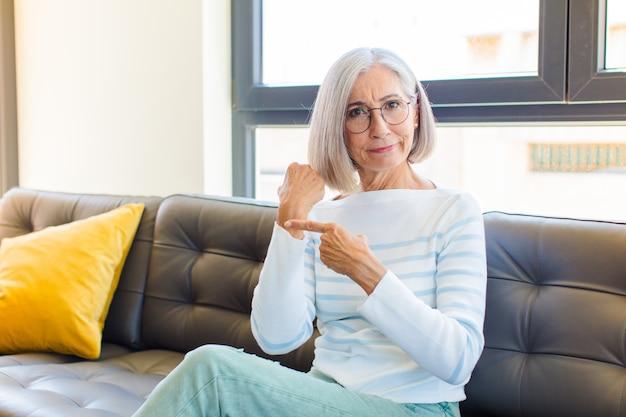 Mulher bonita de meia-idade, impaciente e zangada, apontando para o relógio, pedindo pontualidade, quer ser pontual