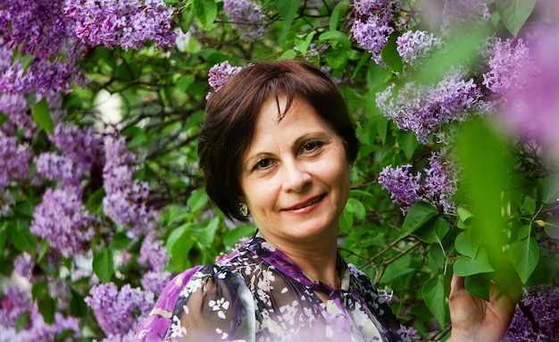 Mulher bonita de meia idade no jardim de flores lilás, sorrindo