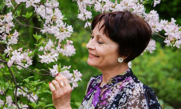 Mulher bonita de meia idade no jardim de iac flores, ooking up, sorrindo